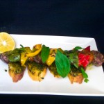 Lamb kebab on basil pesto bruschetta with grilled capsicums