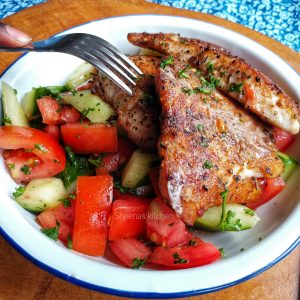 Pan fried fish fillet with tomato and cucumber salad